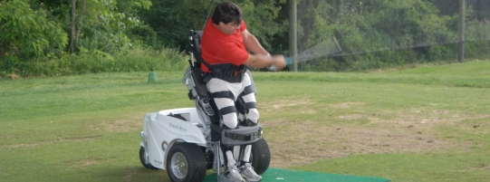 Photo of a man using a specialized assistive golf chair lift while swing a golf club with his left hand he appears to have a spinal ord injury.