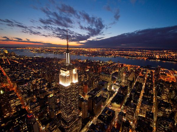 Photo of the new york city skyline from above showing empire state building lit up in white taken at dusk.